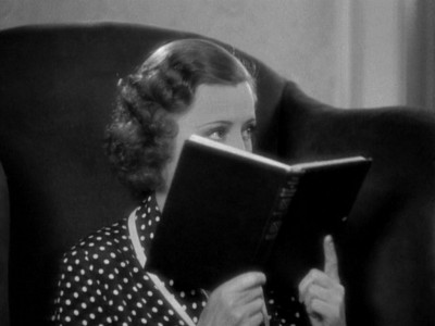 Irene Dunne as Theodora Lynn hiding behind a book
